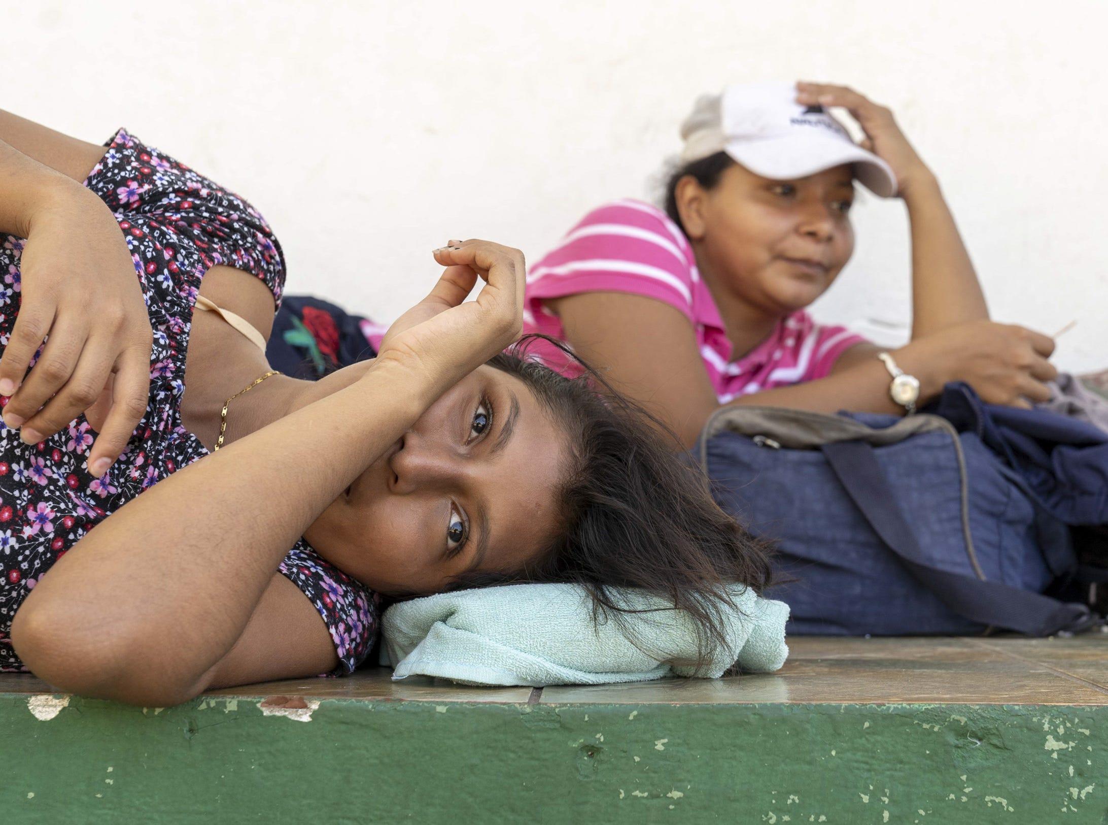 El Salvadoran Angelica Esmeralda Sanchez, 18, front, and her friend Ericka Martinez, 28, gather near a park in Tecun Uman, Guatemala.