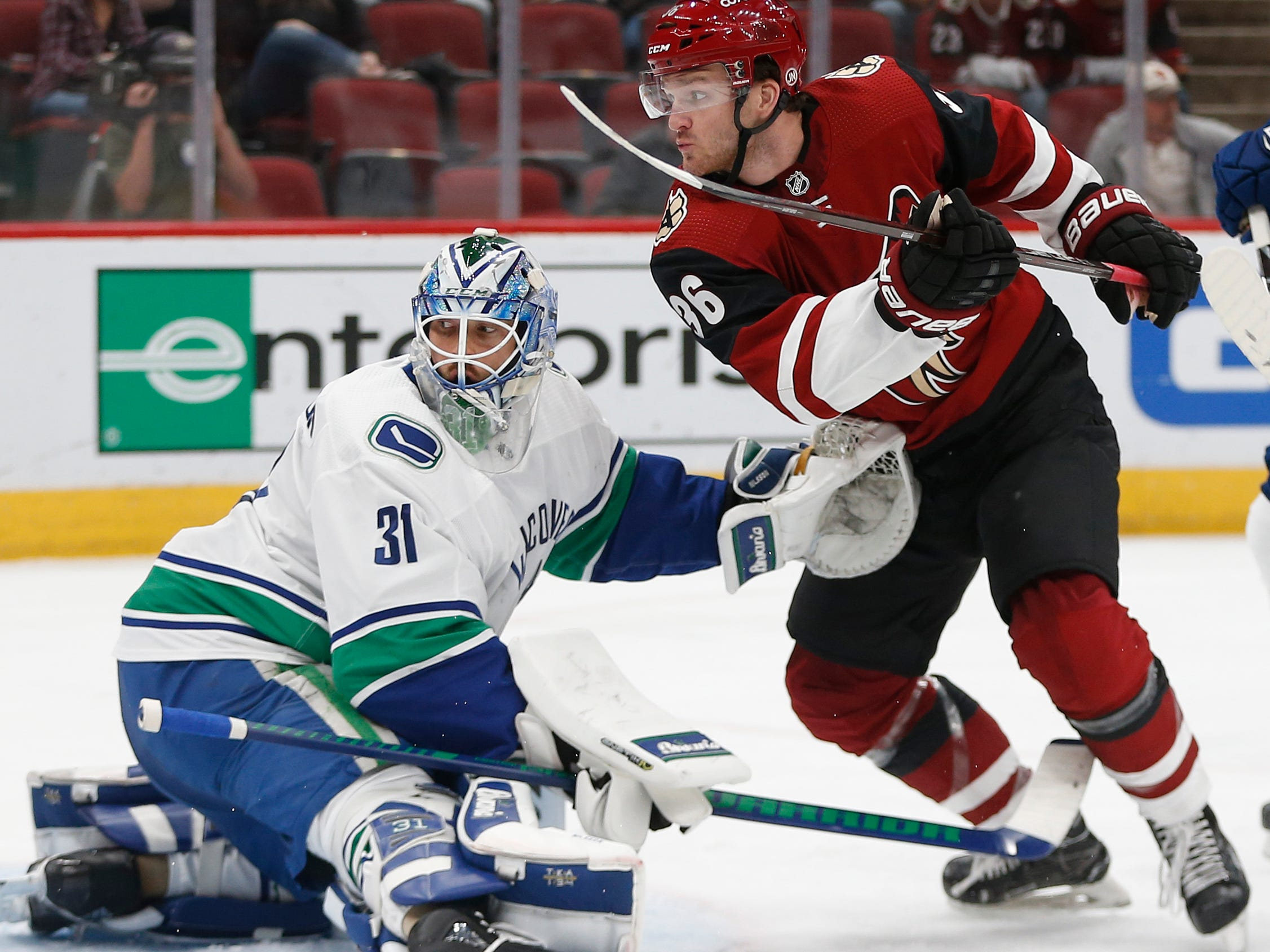 Coyotes' Christian Fischer (36) misses a chance to redirect a shot on Canucks' goalie Anders Nilsson (31) during the first period at Gila River Arena in Glendale, Ariz. on October 25, 2018.