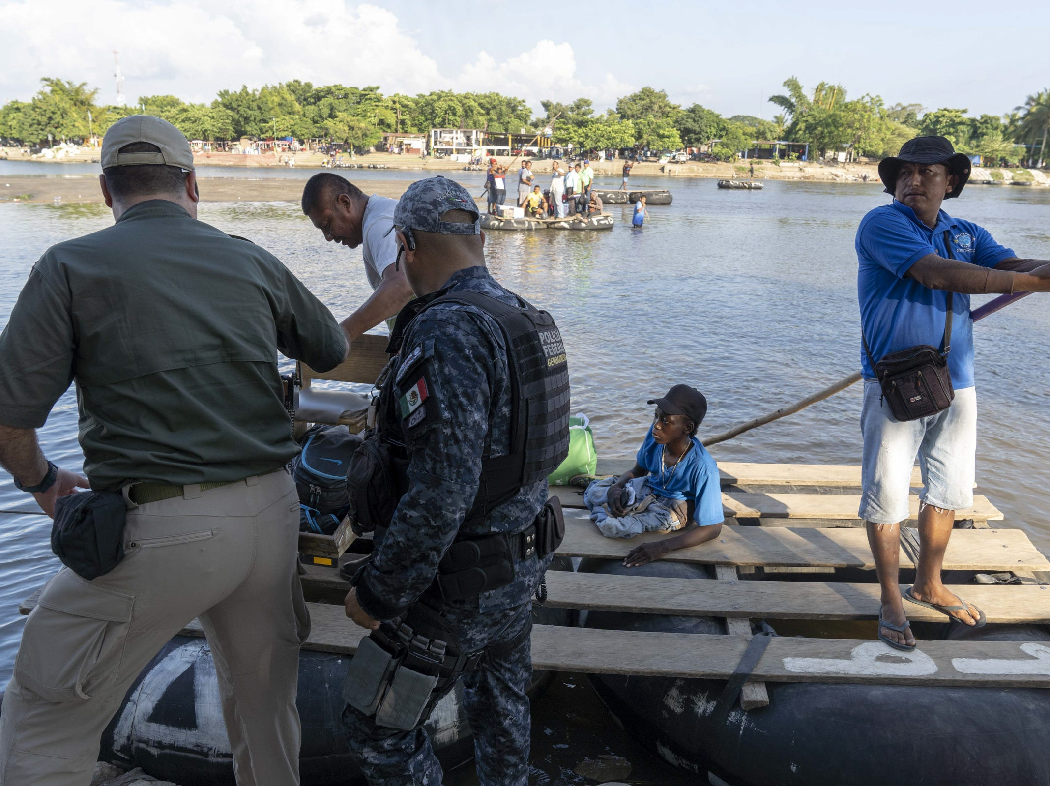 Mexican federal police and immigration officers check the identification of border crossers from Guatemala, who were crossing in a raft at Cuidad Hidalgo, Mexico.