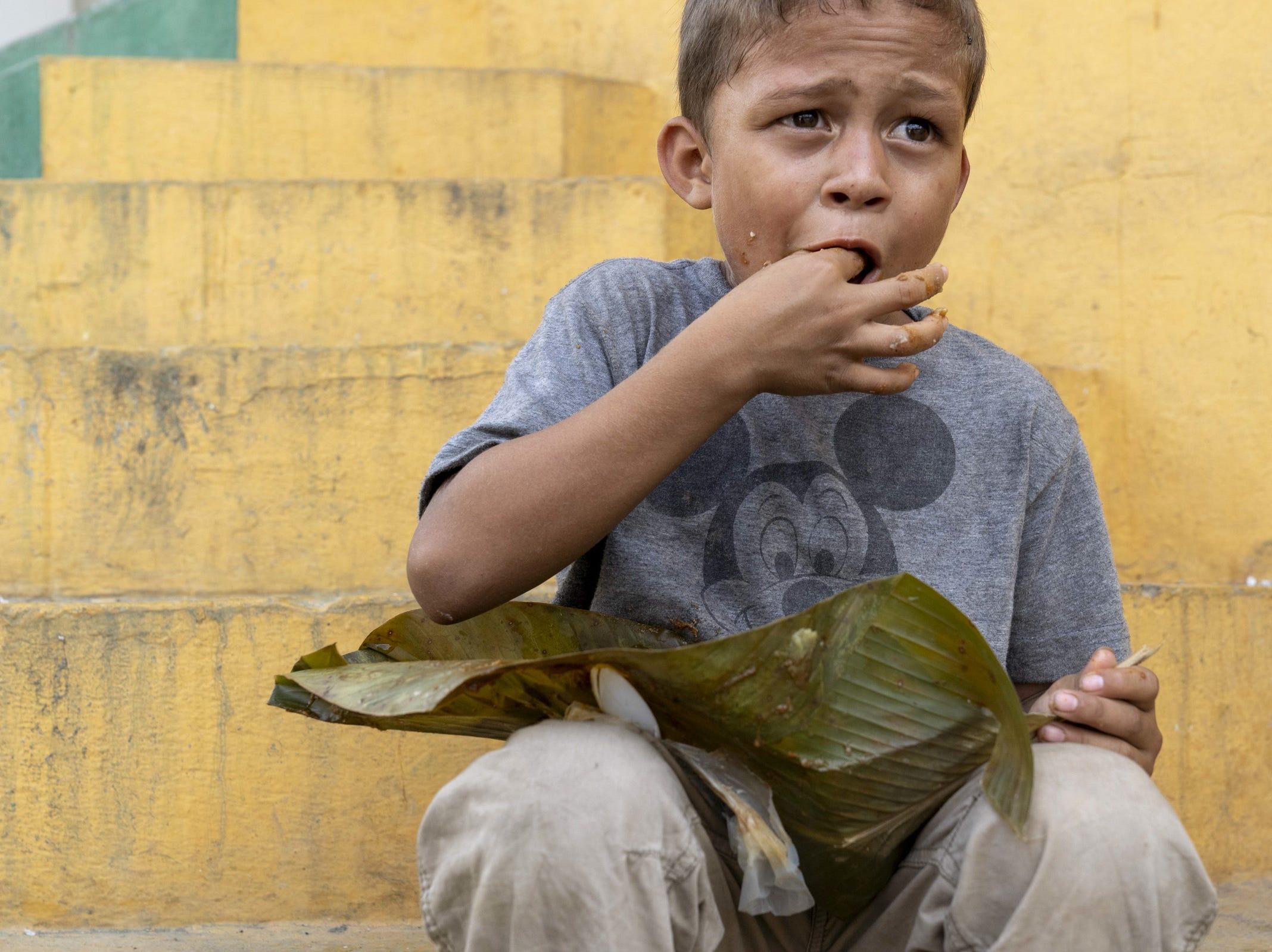 Gerson de Jesus Zelaya, 6, from Honduras, has a donated lunch near a park in Tecun Uman, Guatemala.