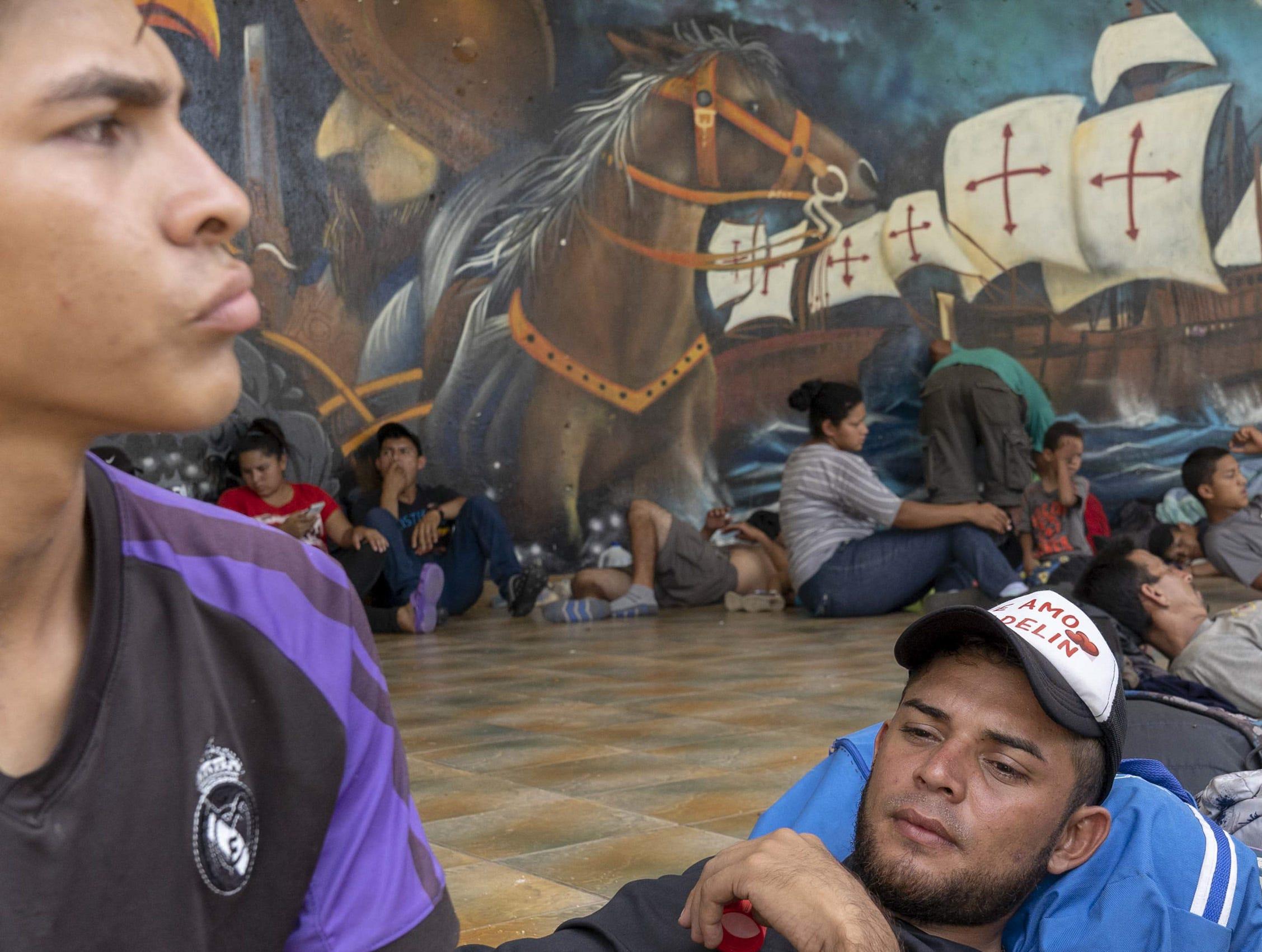 Eduardo Perez, 19, left, and Franklin Eduardo Escobar, 26, from Honduras rest with other migrants near a park in Tecun Uman, Guatemala.