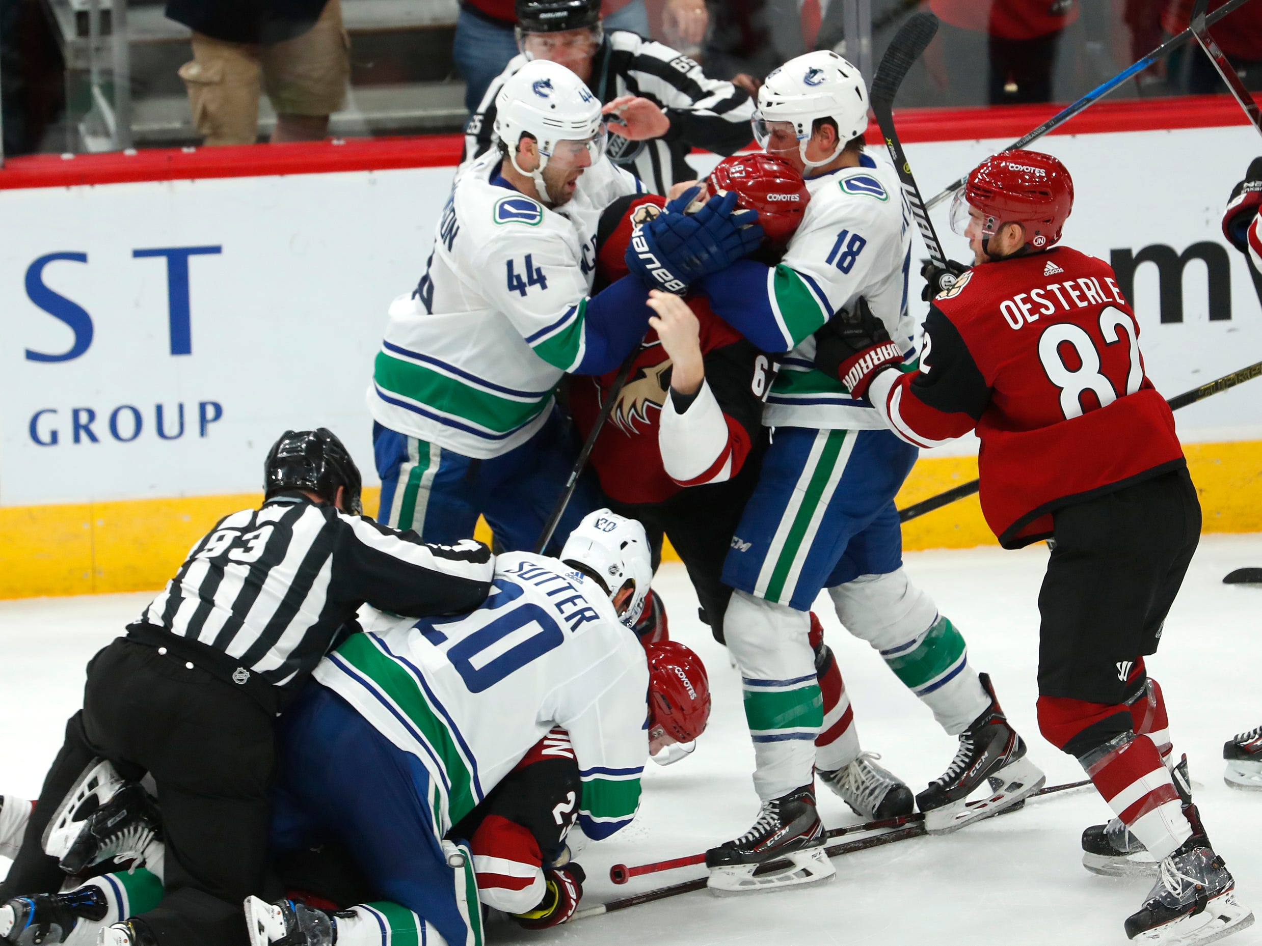Canucks' Erik Gudbranson (44) and Jake Virtanen (18) grab Coyotes' Lawson Crouse (67) by the face as an official tries to pull Canucks' Brandon Sutter (20) off of Coyotes' Oliver Ekman-Larsson (23) during the second period at Gila River Arena in Glendale, Ariz. on October 25, 2018.