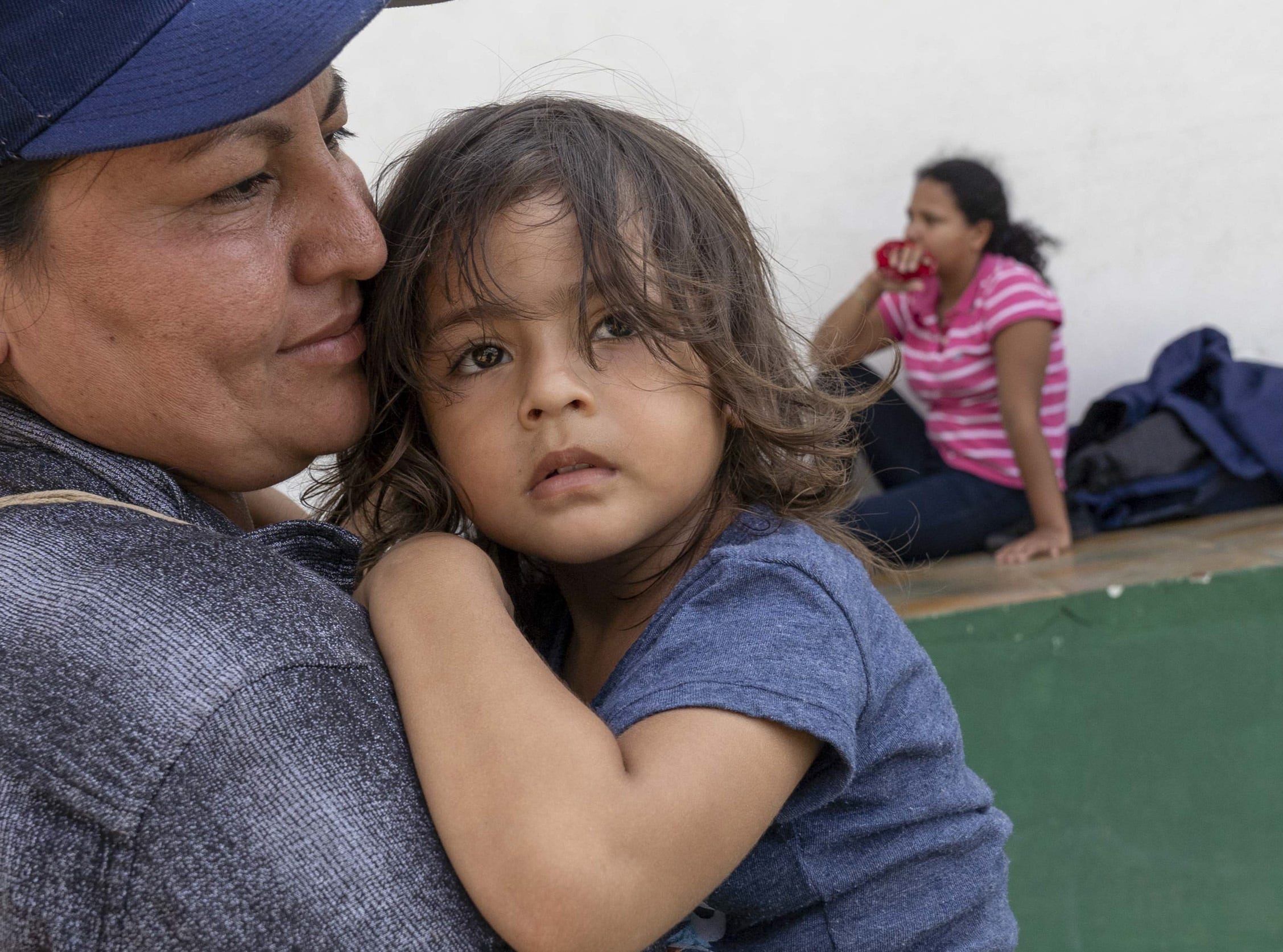 Gabriella Aguilar from Honduras, with her daughter Carmen, waits with other migrants from Honduras and El Salvador near a park in Tecun Uman, Guatemala.