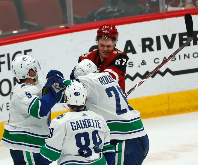 Coyotes' Lawson Crouse (67) fights with Canucks' Antoine Roussel (26) and Derrick Pouliot (5) during the second period at Gila River Arena in Glendale, Ariz. on October 25, 2018.