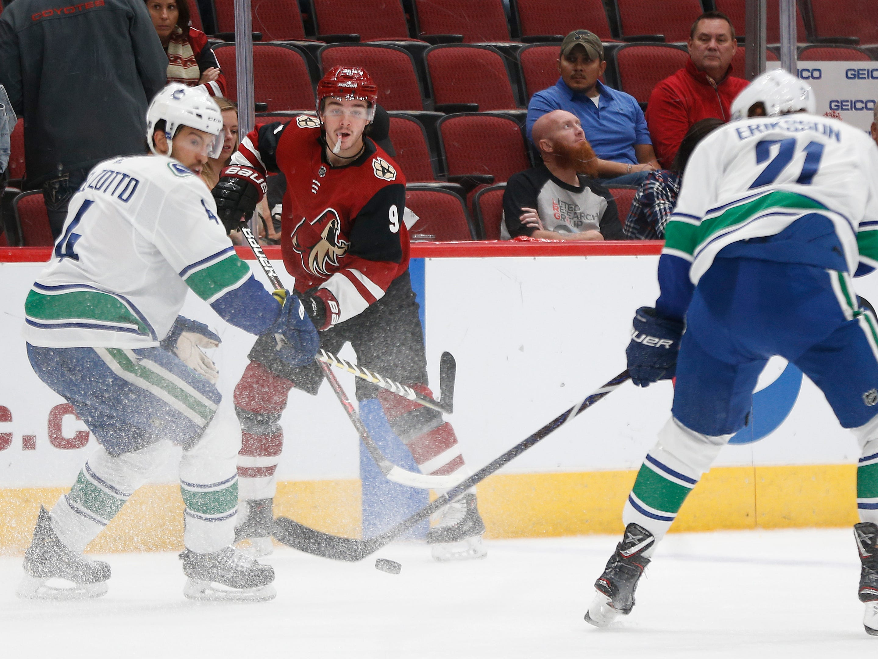 Coyotes' Clayton Keller (9) looks for teammates against Canucks' Michael Del Zotto (4) during the first period at Gila River Arena in Glendale, Ariz. on October 25, 2018.
