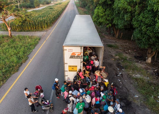 Un grupo de migrantes buscan meterse a la caja de un tráiler.