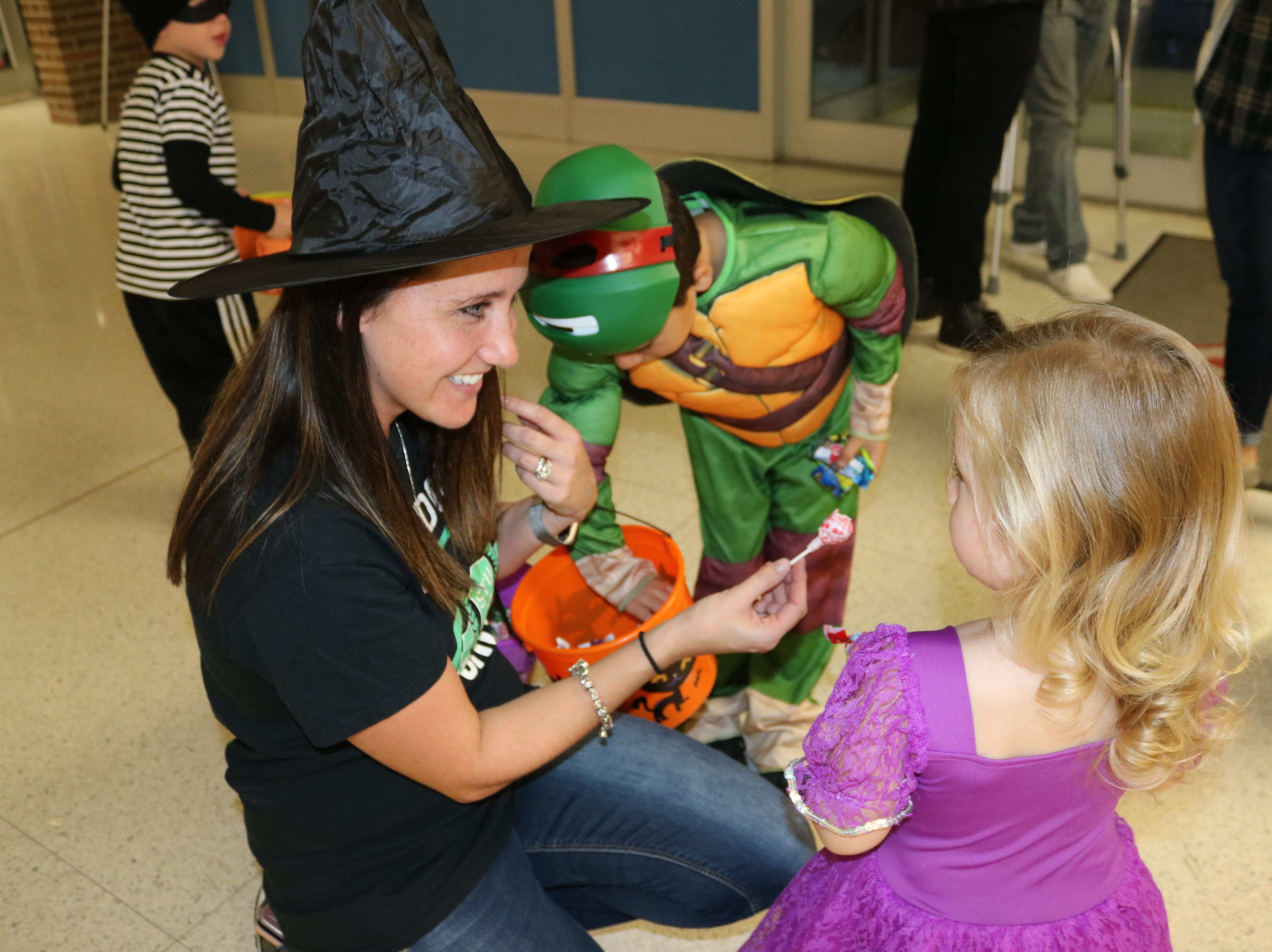"Nikki Wren, student council adviser at Oak Harbor High School, passes out some candy to her own kids during the ""Halloween in the Halls"" event on Thursday."