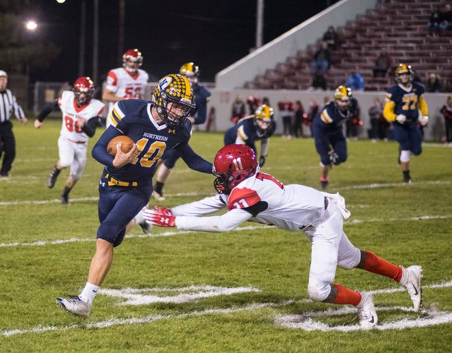 Port Huron Northern quarterback Seth Klink (10) is pushed out of bounds by Lakeshore defensive lineman Devin Shaw during the first quarter of their D2 pre-district tournament game Friday, Oct. 26, 2018 at Memorial Stadium.