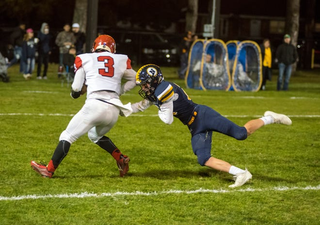 Port Huron Northern defensive back  Nathan Wilson lunges at Lakeshore running back Christian Gaiera (3) during the first quarter of their D2 pre-district tournament game Friday, Oct. 26, 2018 at Memorial Stadium.