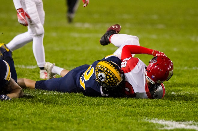 Port Huron Northern defensive back Nathan Wilson (21) tackles Lakeshore tight end Brendan Colley in the first quarter of their D2 pre-district tournament game Friday, Oct. 26, 2018 at Memorial Stadium.