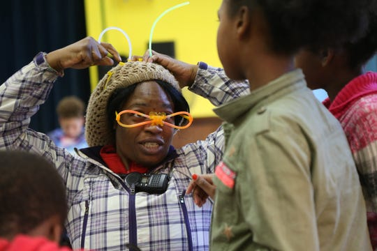 Kadian Denton shows students in the Krieger Elementary School after school program some ideas for crafting with their light sticks during the Family Services' Lights on Afterschool rally at Krieger Elementary School in the City of Poughkeepsie on October 25, 2018.