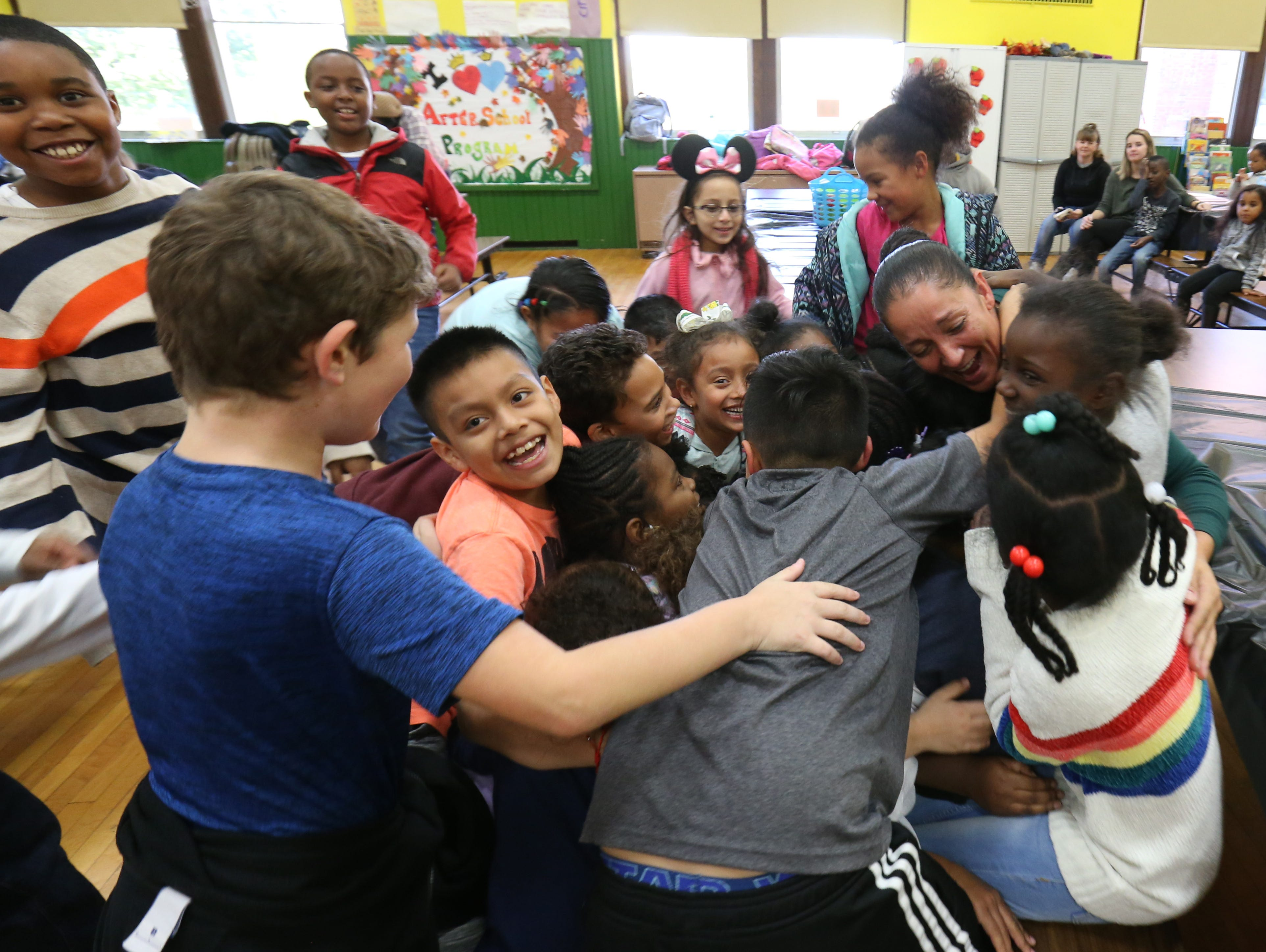 Students who participate in the after school program at Krieger Elementary School surround and hug after school program site supervisor Daisy Lee on October 25, 2018.