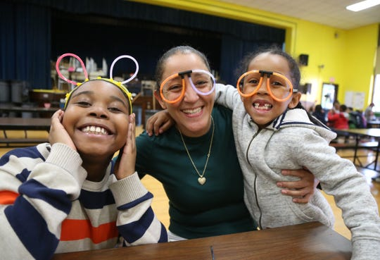 From left, Ri-Mir Parker, Daisy and Pharaoh Lee shows off their glow stick creations during the Family Services' Lights on Afterschool rally at Krieger Elementary School in the City of Poughkeepsie on October 25, 2018. Daisy Lee is the aterschool program supervisor for Krieger Elementary.