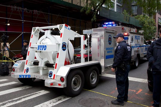 A police truck tows a total containment vessel to a post office in midtown Manhattan to dispose of a suspicious package, Friday, Oct. 26, 2018, in New York.  Two law enforcement officials say a package closely resembling parcels sent to critics of President Donald Trump has been found at the postal facility in Manhattan.  The suspicious package was discovered by postal workers. (AP Photo/Mark Lennihan)