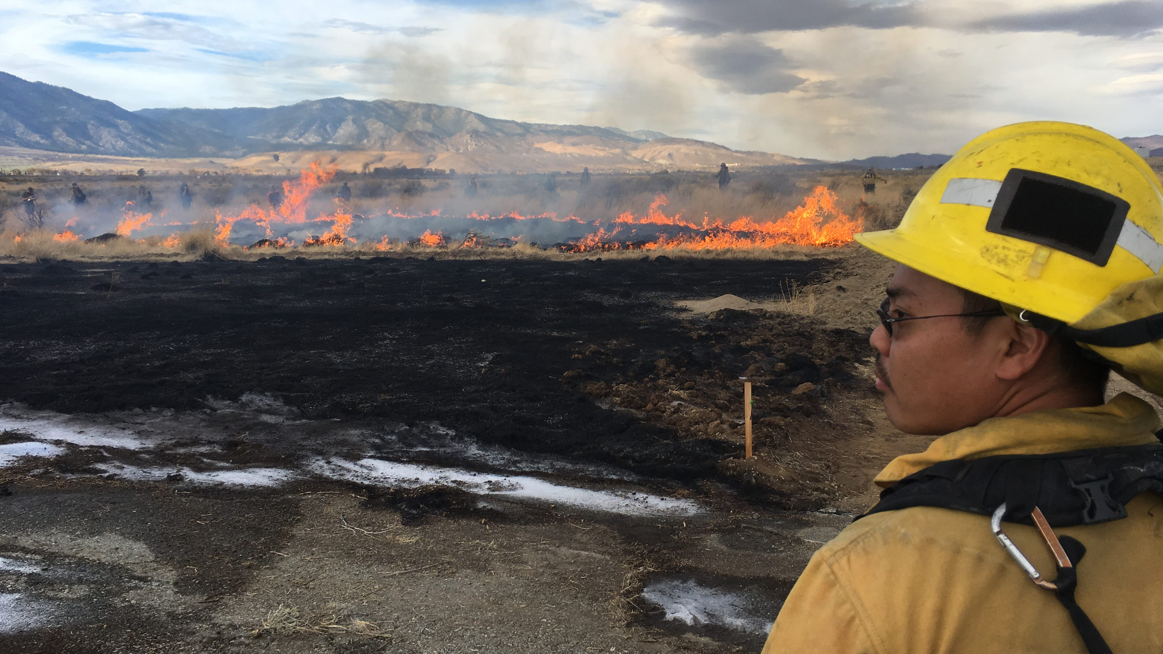 A firefighter watches over a fire in Minden, Nev., on Oct. 24, 2018 that was intentionally set as part of a training course for wildland fire origin and cause investigators.