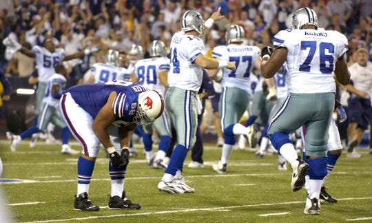 Bills lineman Langston Walker bends over in dejection as the Cowboys celebrate their last-second field goal on Monday Night Football.