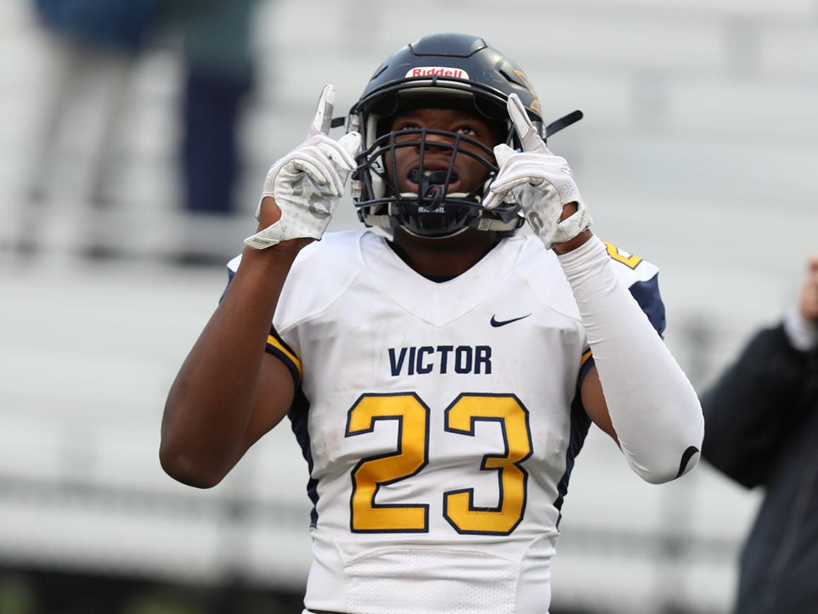 Victor's Rushawn Baker points to the sky after scoring a touchdown.