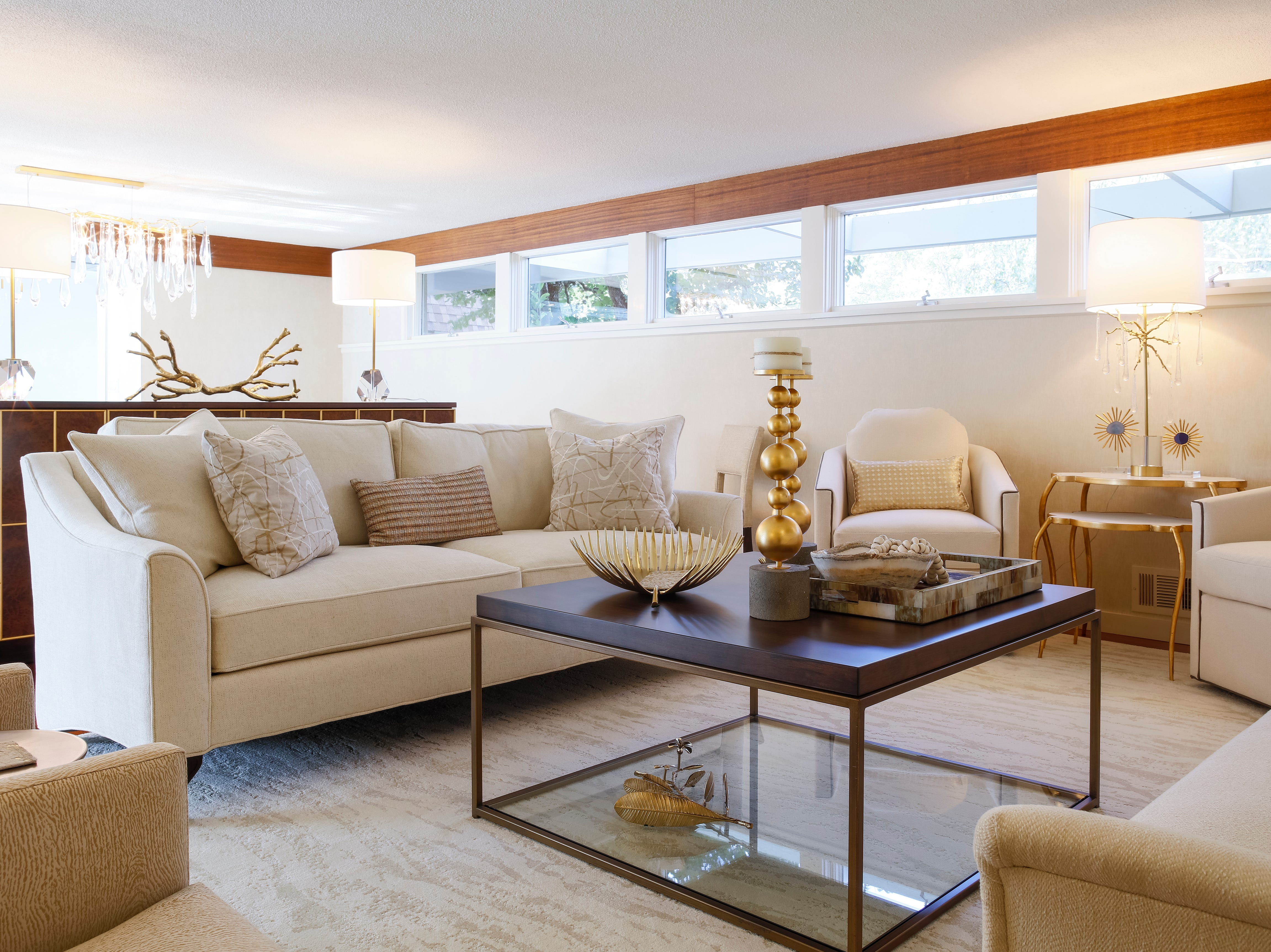 The living room is warm and comfortable with its mix of white furnishings accented with gold finishes and warm wood.