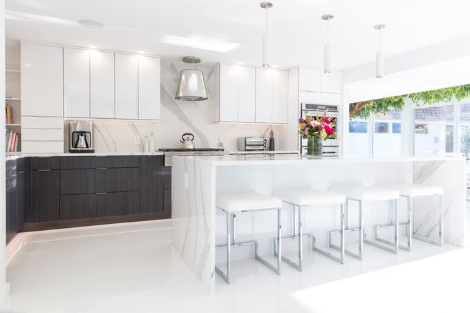 The mostly white kitchen has a large quartz island.