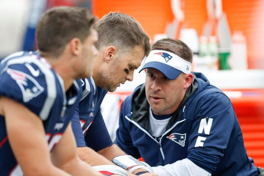 New England Patriots quarterback Tom Brady (12) talks with offensive coordinator Josh McDaniels.