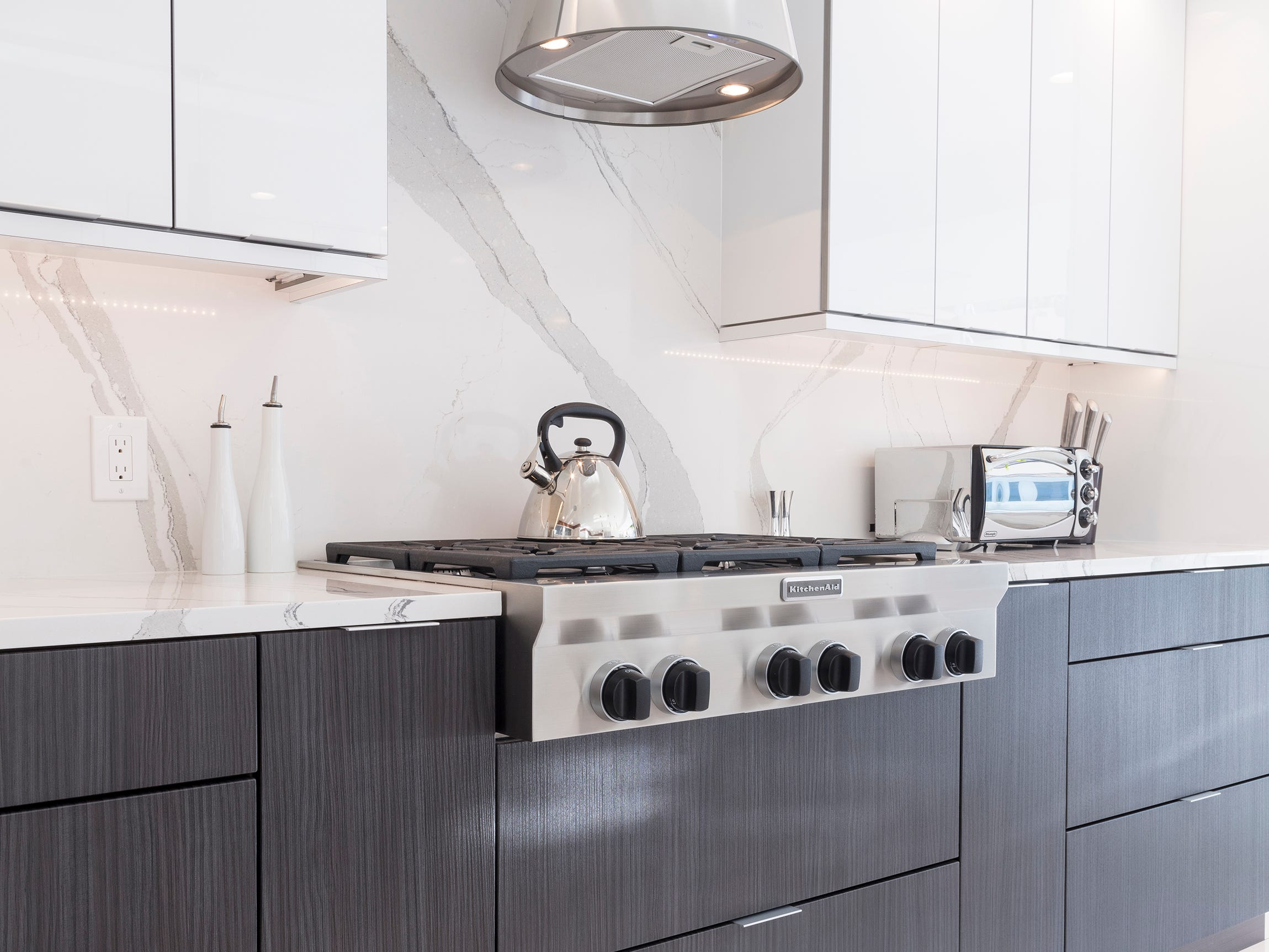 The slab backsplash matches the quartz island.