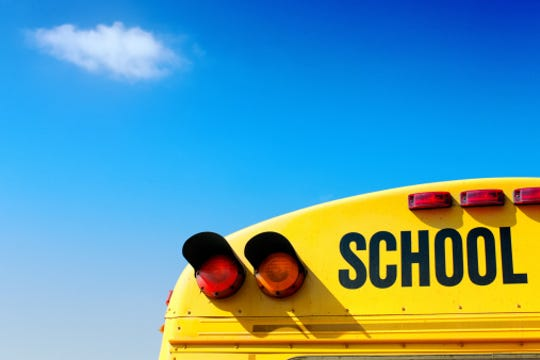 Yellow school bus against vivid blue sky.