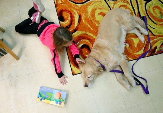 Adriana Venable, 4, pats therapy dog Bailey at the Mary Cariola Children's Center. She goes there for a day program including occupational and physical therapy and speech therapy, among other things.