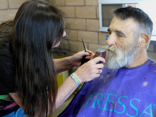 Eileen Ford trims Michael Dopp's beard Friday at the North Valley Stand Down in Anderson.