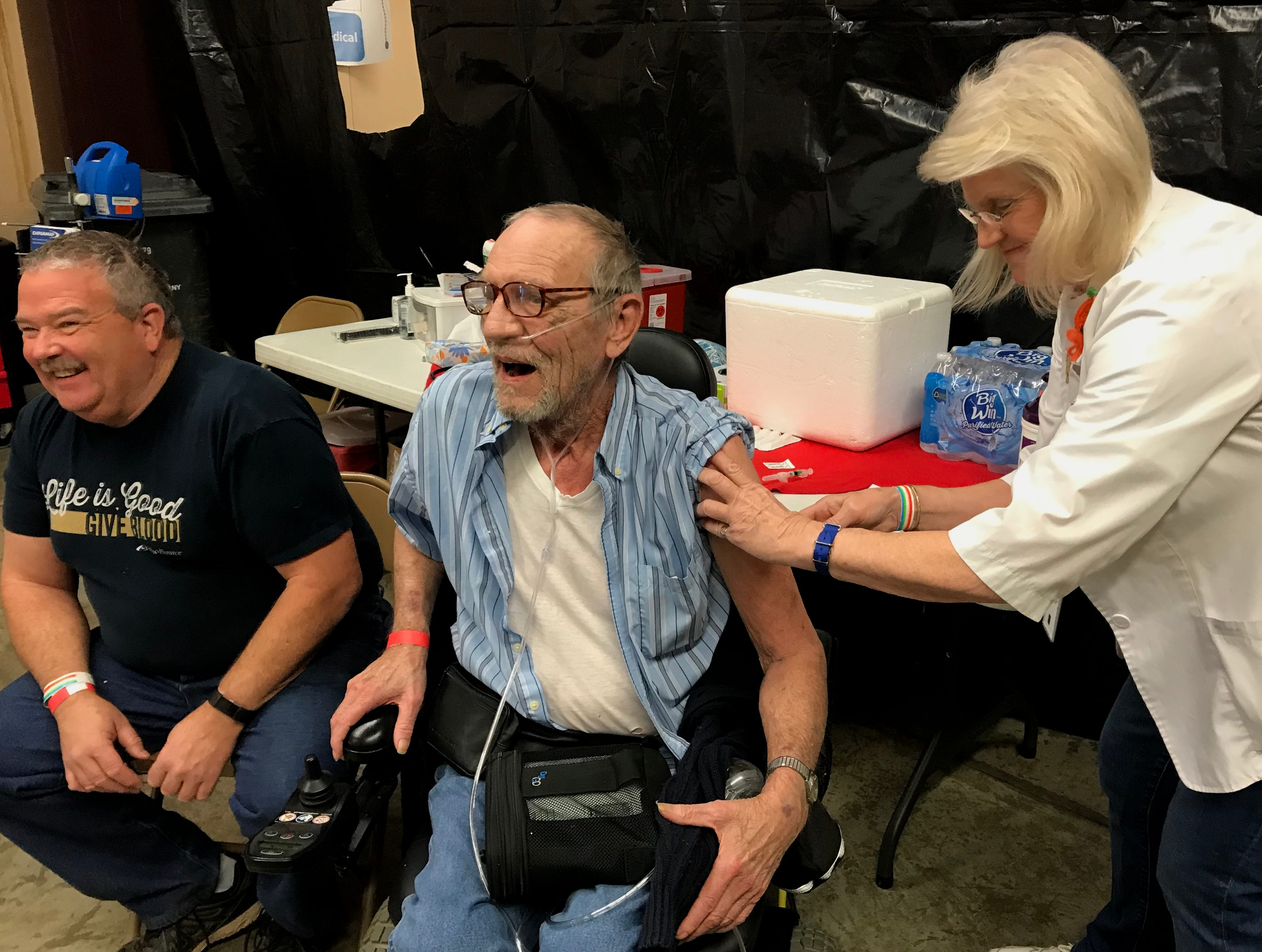 Neal Myers, a 59-year-old U.S. Navy veteran, and 72-year-old Don Madsen, an Army vet, got their flu shots at the North Valley Stand Down.