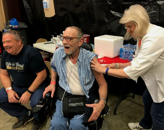 Neal Myers, a 59-year-old U.S. Navy veteran, and 72-year-old Don Madsen, an Army vet, receive their flu shots at the North Valley Stand Down in October 2018.