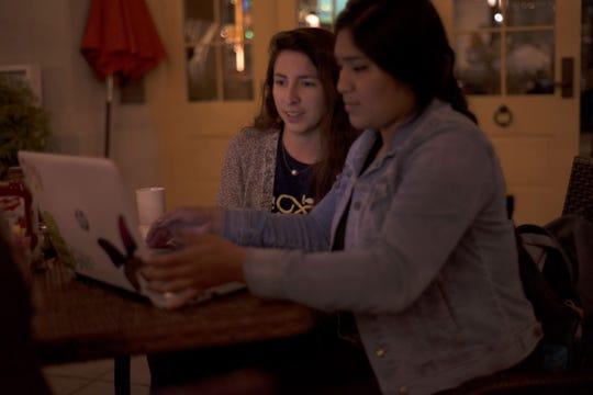 Anita García, izquierda, organizadora del capítulo de Girl Develop It, le enseña a Angie Guevara, derecha, los conocimientos básicos para codificar un sitio web en Portobellos en Salinas, el 17 de octubre.