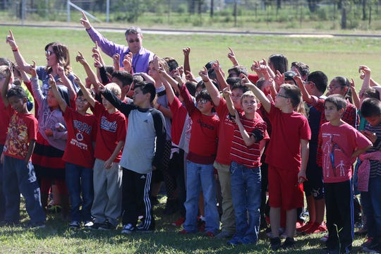Grape Creek ISD students raise their hands for their school song Friday, Oct. 26, 2018 at the district's ground breaking for its new middle school campus.