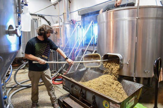 Andrew Lovelass pulls spent grains out of the mash tank at the Burley Oak Brewery in Berlin on Wednesday, Oct 24, 2018.