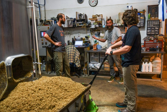 Adam Davis, Bryan Brushmiller and Andrew Lovelass chat while working on a new batch of Lost IPA at the Burley Oak Brewery in Berlin on Wednesday, Oct 24, 2018.