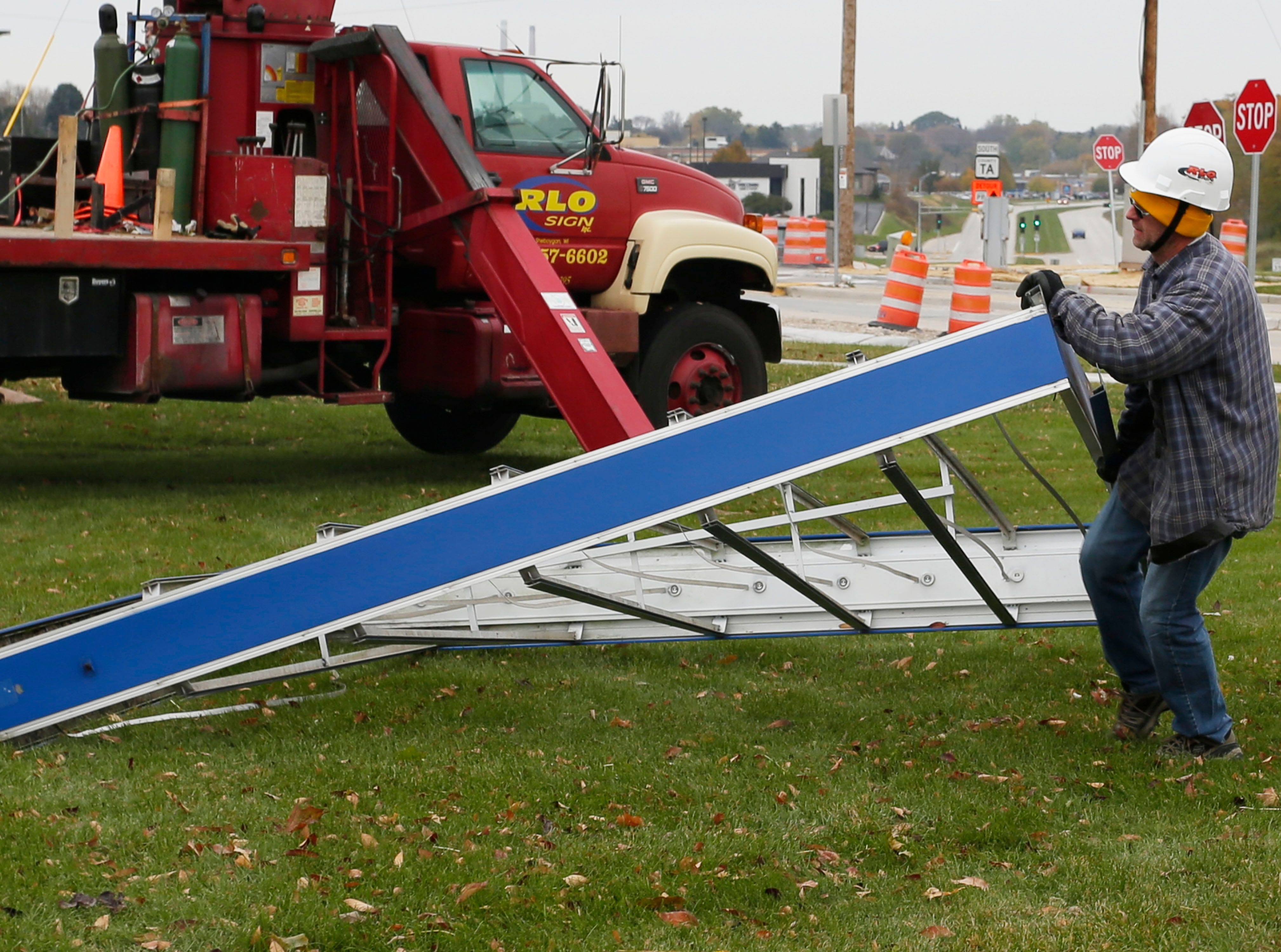 RLO Signs' Fred Bertram moves a sign frame while dismantling the iconic Sheboygan Memorial Mall, Friday, October 26, 2018, in Sheboygan, Wis.