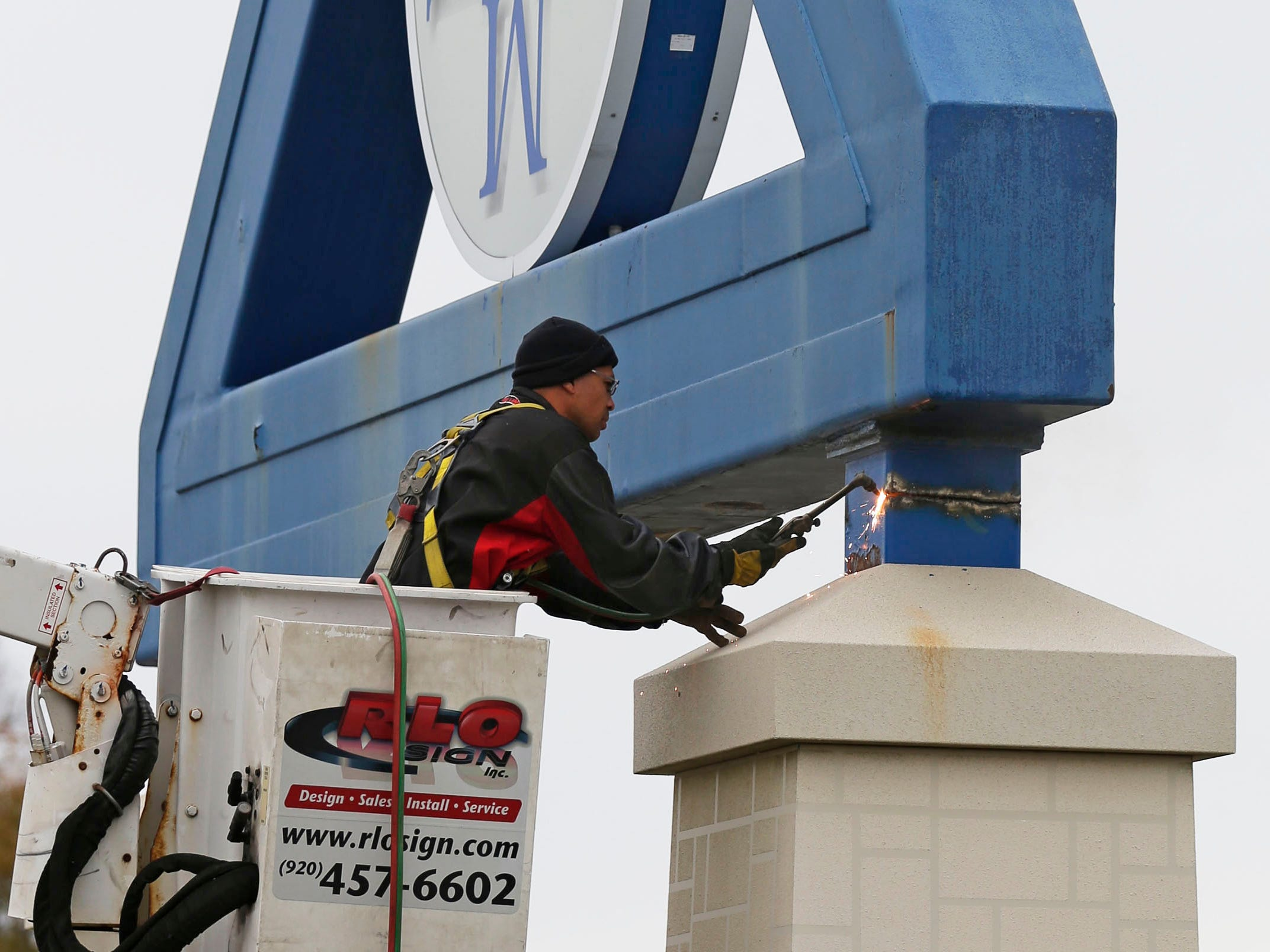 Sparks spatter as RLO Signs' Tom Peschong uses a cutting torch to dismantle the iconic Sheboygan Memorial Mall sign, Friday, October 26, 2018, in Sheboygan, Wis. A new sign by Meijers is replacing the iconic old sign.