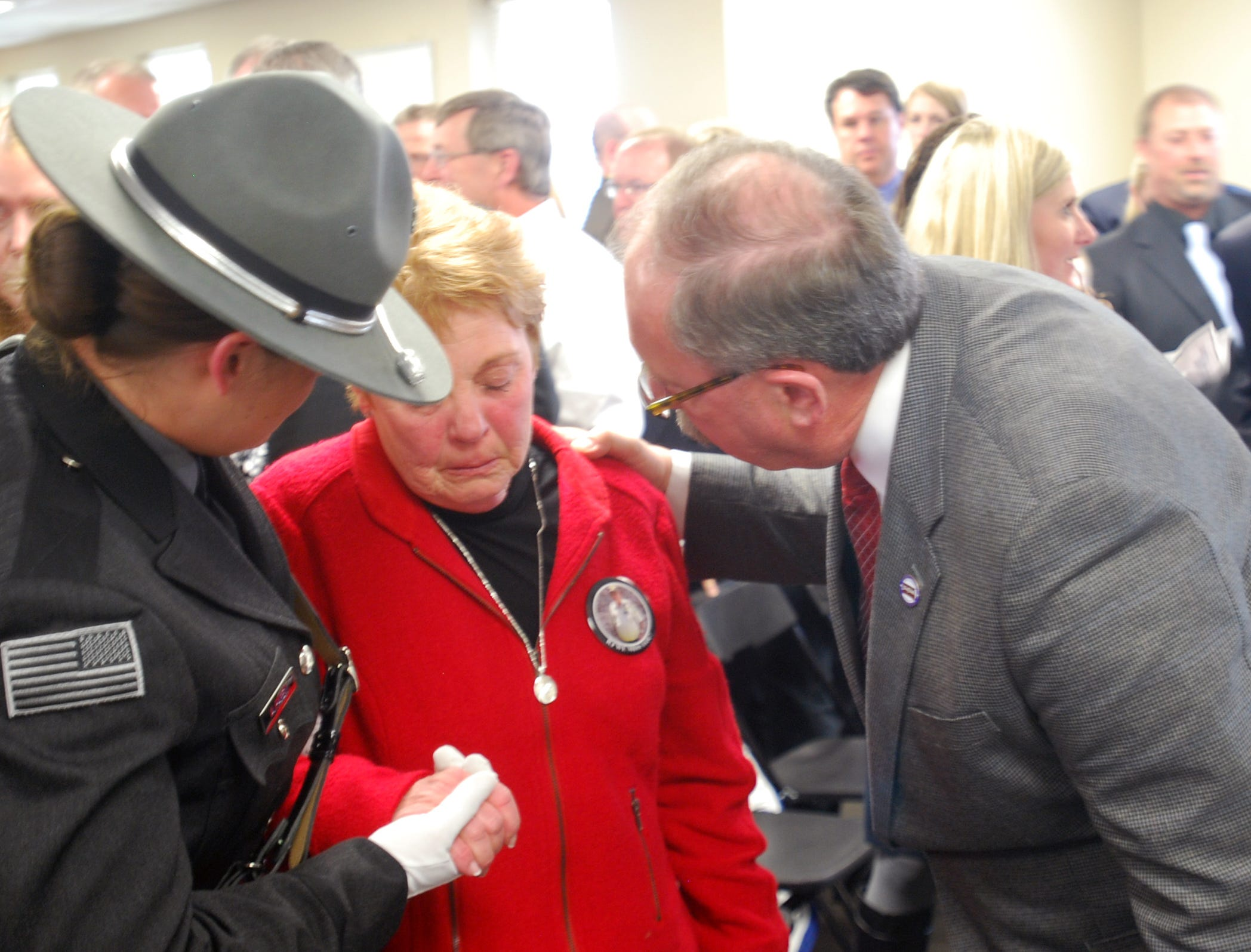"""A member of the South Dakota Department of Corrections Honor Guard and state penitentiary prison Warden Doug Weber with Lynette Johnson at the dedication of penitentiary training academy in honor of her late husband Ron """"RJ"""" Johnson. The dedication was Thursday, April 12, a year after Johnson was killed while on duty by two inmates. More than 100 people were on hand for the dedication."""