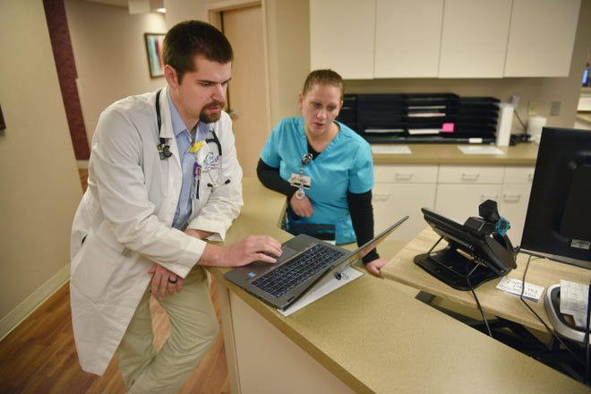 Dr. Joseph Swedzinski meets with RN Cindy Genzler before he sees a patient Tuesday, Oct. 23, at the Center for Family Medicine in Sioux Falls. Dr. Swedzinski is in the USD residency program.