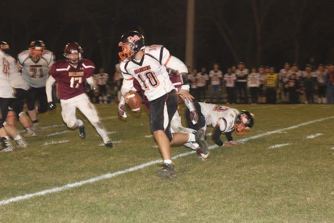 Dell Rapids quarterback Eddie Price  tries to elude Madison's Caileb Reilly in the fourth quarter of Thursday's quarterfinal game.