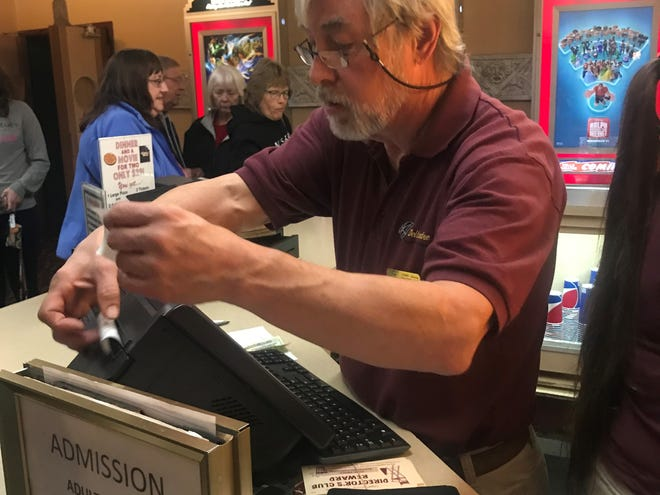 Steve Howard, a manager at Dells Theatre, helps customers on Oct. 24.