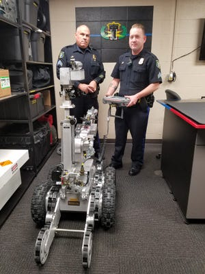 Two Sioux Falls Police Department officers pose with the department's new bomb squad robot.