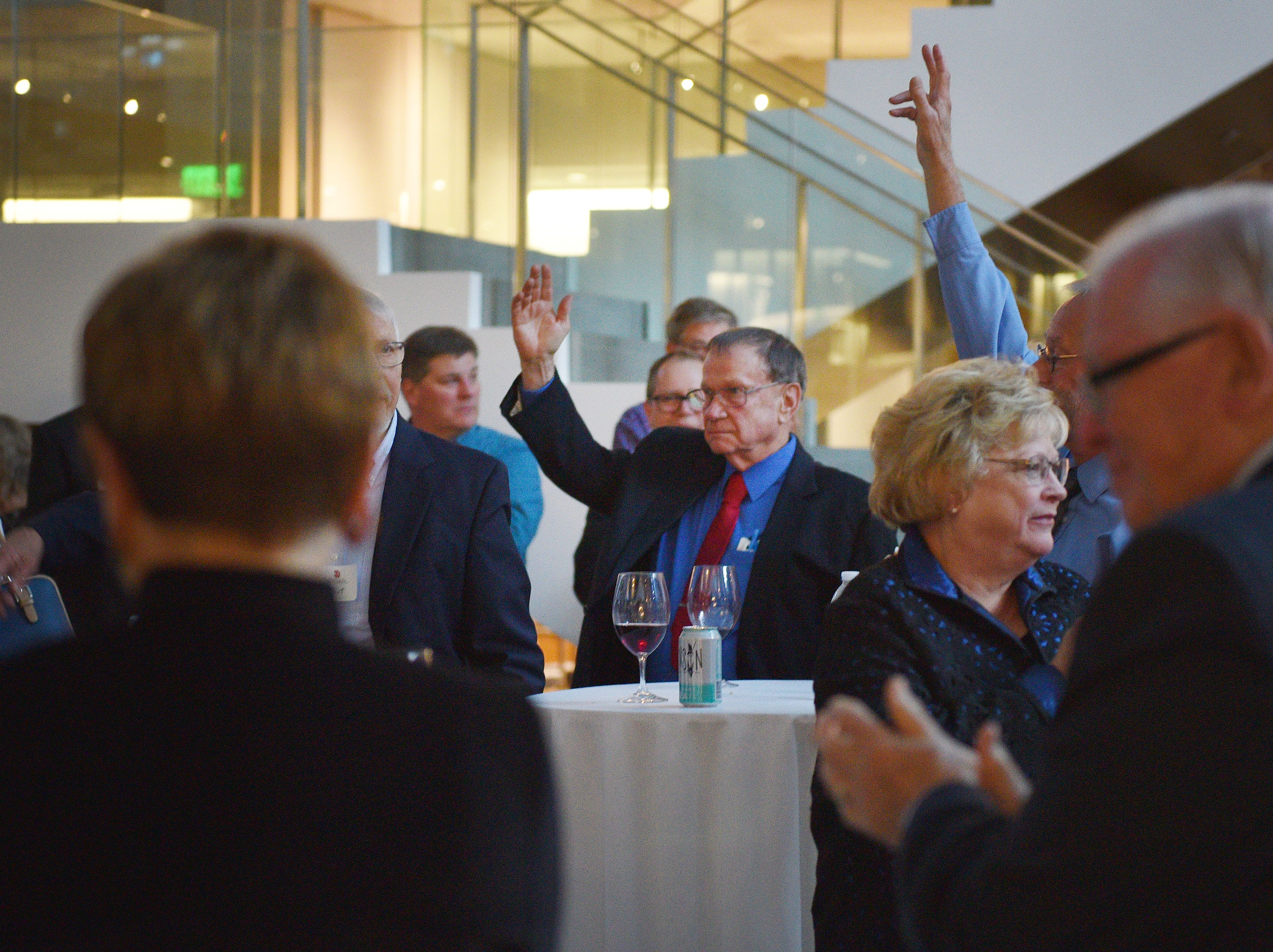 USD residency alumni raise their hands to be recognized at the 60th Anniversary celebration Wednesday, Oct. 24, at Sanford Imagenetics in Sioux Falls.