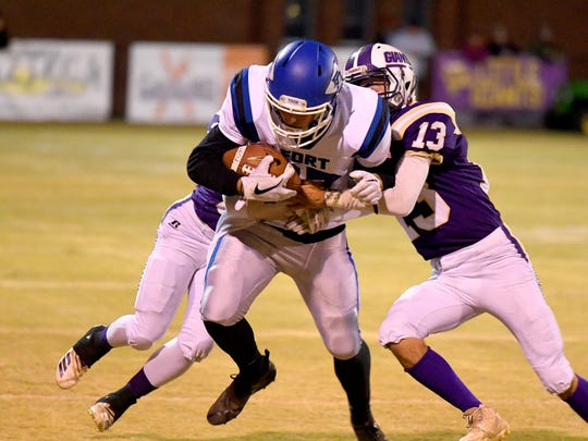 Fort Defiance's Bryce Owens protects the ball and fights for more yards as Waynesboro's Jeremy Henderson wraps him up from behind while Ethan Burch gets in on the tackle from the side during a game played in Waynesboro on Thursday, Oct. 25. 2018.
