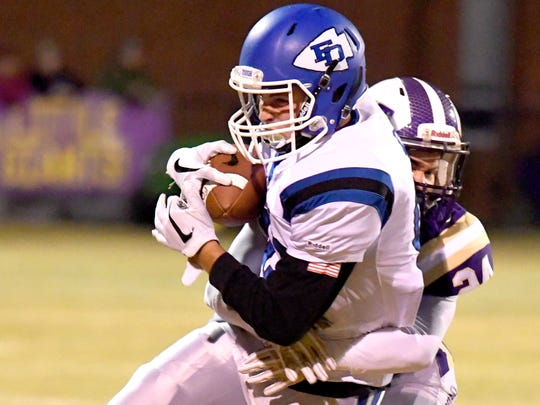 Fort Defiance's Bryce Owens protects the ball as Waynesboro's Jeremy Henderson wraps him up from behind during a game played in Waynesboro on Thursday, Oct. 25. 2018.