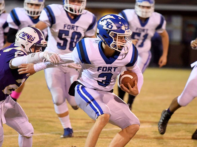 Fort Defiance's Cole Sligh is forced to pause in his run with the ball allowing Waynesboro's Jeremy Henderson to grab onto his arm during a game played in Waynesboro on Thursday, Oct. 25. 2018.