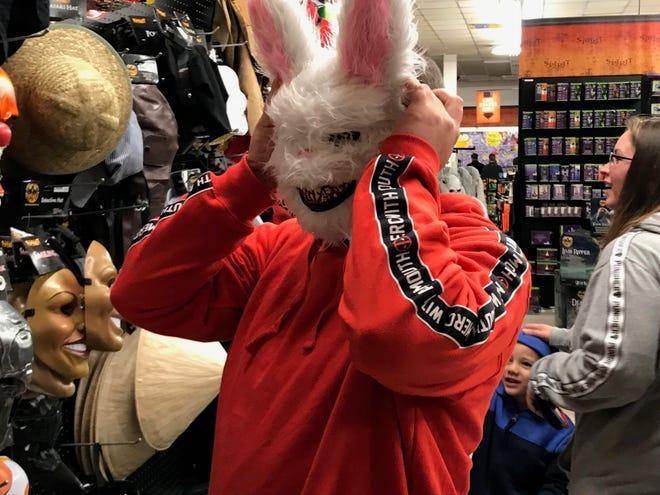 Timmy Wheeler, of Waynesboro, tries on a mask Friday at Spirit Halloween in Waynesboro.