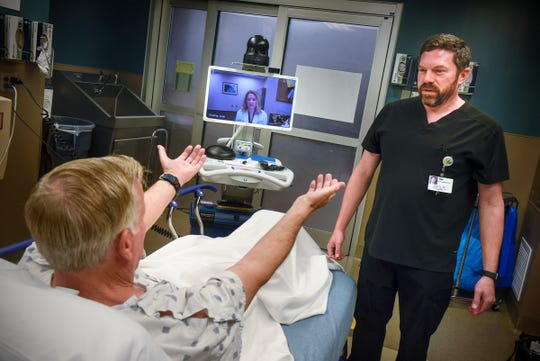 RN Brad Rourke works with Ray Davidson as nurse practicioner Leah Roering observes during a demonstration of the TeleStroke system Friday, Oct. 26, at the St. Cloud Hospital.