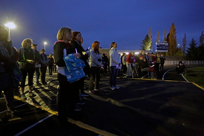 Attendees listen to a speaker at a vigil for slain Pullman High School graduate and University of Utah communications major and track athlete, Lauren McCluskey, Wednesday, Oct. 24, 2018, in Pullman, Wash. Police said Melvin Rowland, 37, fatally shot 21-year-old McCluskey of Pullman, on Monday night on the university campus and then killed himself in a church as officers closed in. (Kai Eiselein/The Moscow-Pullman Daily News via AP)