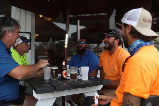 Rich Turnball, left, Bruce Kreis, Martyn Carree, Chris Muskett and Travis Turnball, volunteers with the Rotary Club of St. Augustine Beach take a break from lunch at the Apalachicola Seafood Grill in downtown Apalachicola, Fla. two weeks after Hurricane Michael hit the coastal town Thursday, Oct. 25, 2018.
