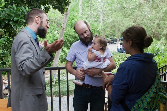 Rev. William Levwood talks to a family after a service at Unitarian Universalist Church.